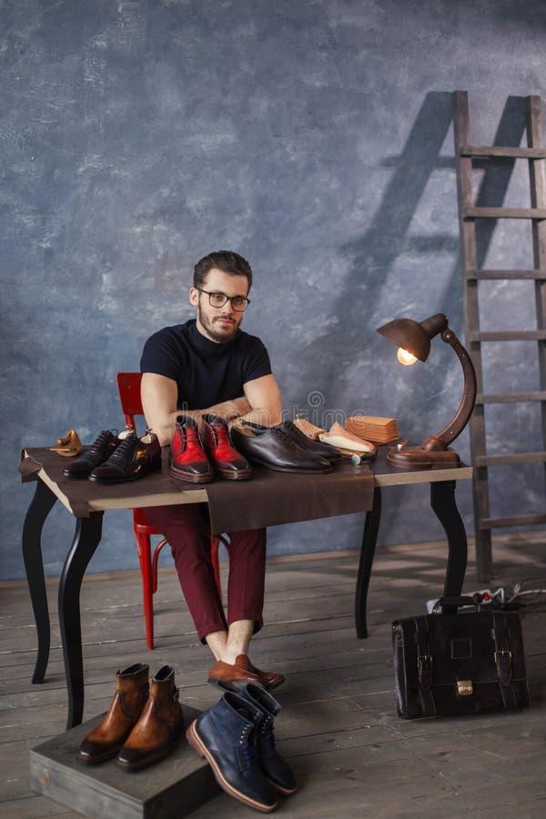 Attraktiv skomakare som sitter på tabellen med reparerade skor royaltyfri foto