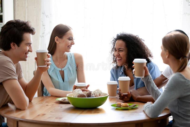 Attraktiv skratta flicka för blandat lopp som har gyckel med vänner i kafé arkivfoto