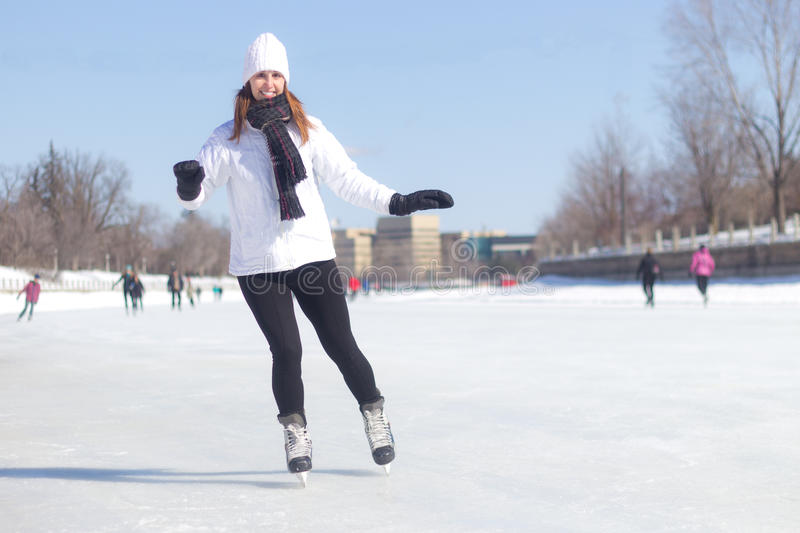 Attraktiv skridskoåkning för ung kvinna under vinter arkivbild