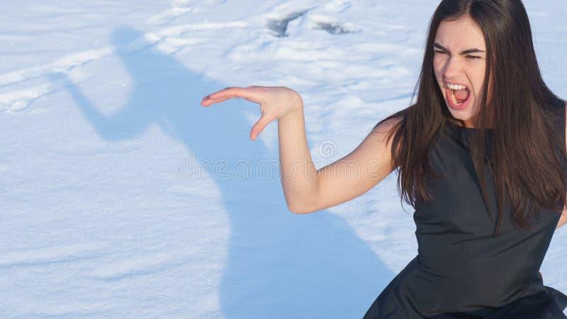 Attraktiv skrikig ung brunettflicka för stående på en snöig bakgrund med skugga royaltyfria foton