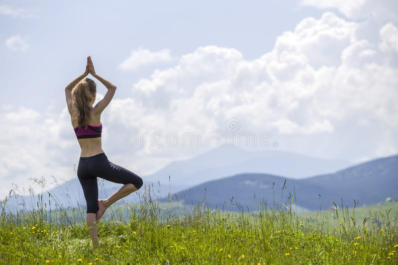 Attraktiv slank ung kvinna som utomhus gör yogaövningar på bakgrund av gröna berg på solig sommardag arkivfoton