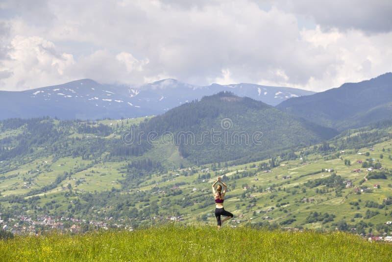 Attraktiv slank ung kvinna som utomhus gör yogaövningar på bakgrund av gröna berg på solig sommardag royaltyfri bild
