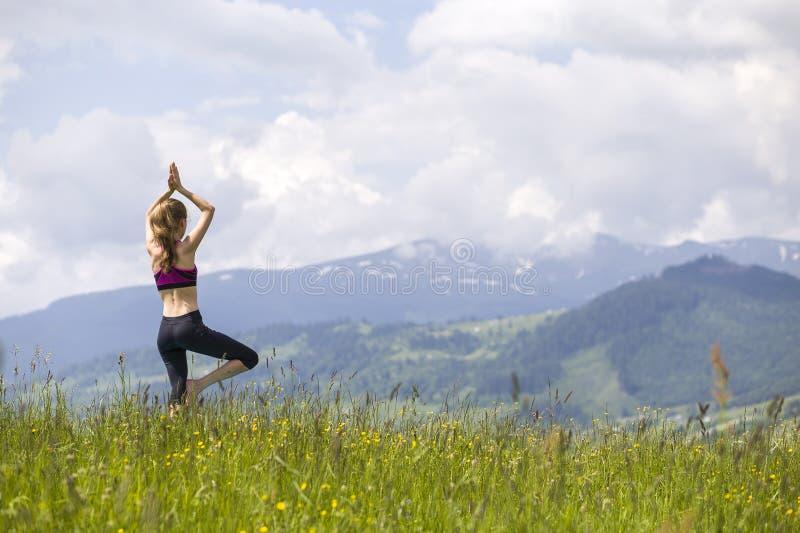 Attraktiv slank ung kvinna som utomhus gör yogaövningar på bakgrund av gröna berg på solig sommardag royaltyfria foton