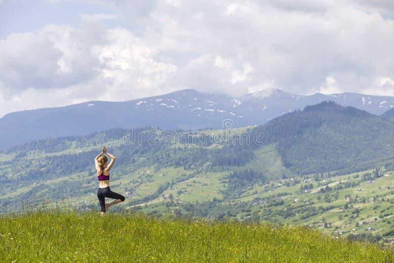Attraktiv slank ung kvinna som utomhus gör yogaövningar på bakgrund av gröna berg på solig sommardag royaltyfri foto