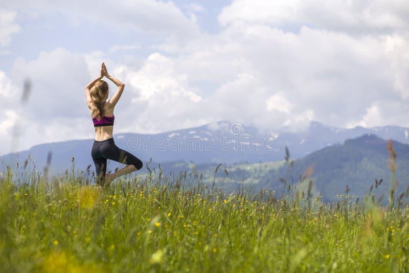 Attraktiv slank ung kvinna som utomhus gör yogaövningar på bakgrund av gröna berg på solig sommardag royaltyfria bilder