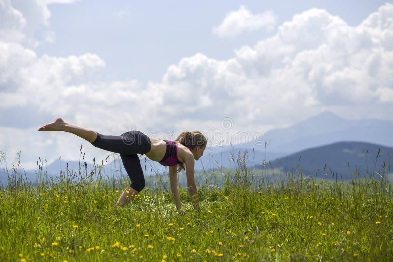 Attraktiv slank ung kvinna som utomhus gör yogaövningar på kopieringsutrymmebakgrund av berg arkivfoton