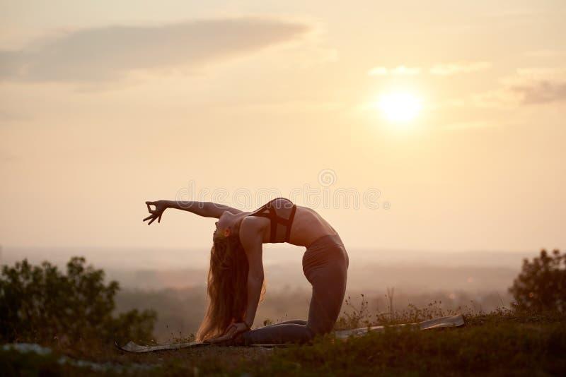 Attraktiv slank ung kvinna som utomhus gör yogaövningar på kopieringsutrymmebakgrund av härlig himmel arkivfoto