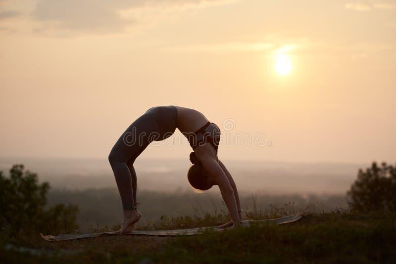 Attraktiv slank ung kvinna som utomhus gör yogaövningar på kopieringsutrymmebakgrund av härlig himmel fotografering för bildbyråer