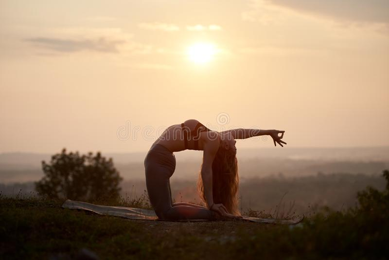 Attraktiv slank ung kvinna som utomhus gör yogaövningar på kopieringsutrymmebakgrund av härlig himmel royaltyfri foto