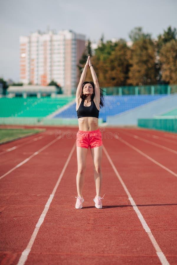 Attraktiv sportig brunettkvinna i rosa kortslutningar och bästa görande genomkörare med hopprepet i solstrålar på stadion royaltyfria bilder