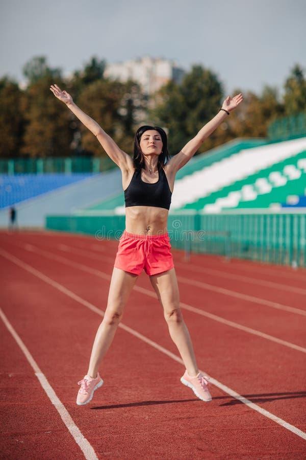Attraktiv sportig brunettkvinna i rosa kortslutningar och bästa görande genomkörare med hopprepet i solstrålar på stadion royaltyfri bild