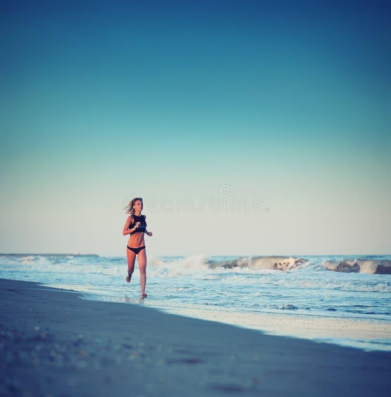 Attraktiv sportig flicka med snabb spring längs stranden på den fantastiska solnedgången med havet på bakgrund royaltyfri foto