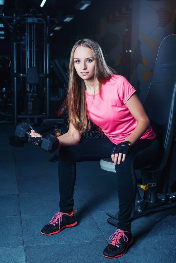 Attraktiv sportig flicka som gör genomkörare med hantlar i idrottshall Härlig konditionkvinna som arbetar på hennes biceps royaltyfri bild