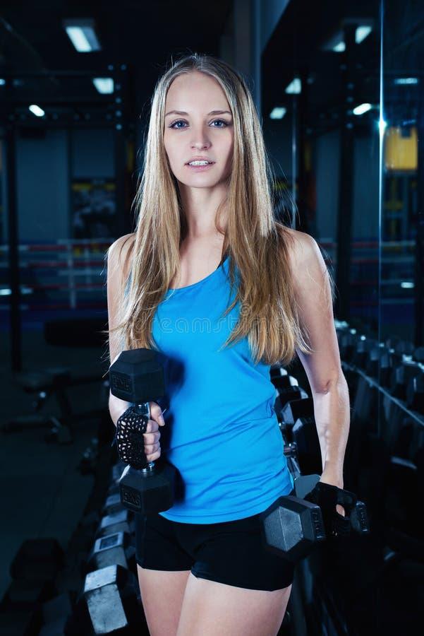 Attraktiv sportig flicka som gör genomkörare med hantlar i idrottshall Härlig konditionkvinna som arbetar på hennes biceps arkivfoto