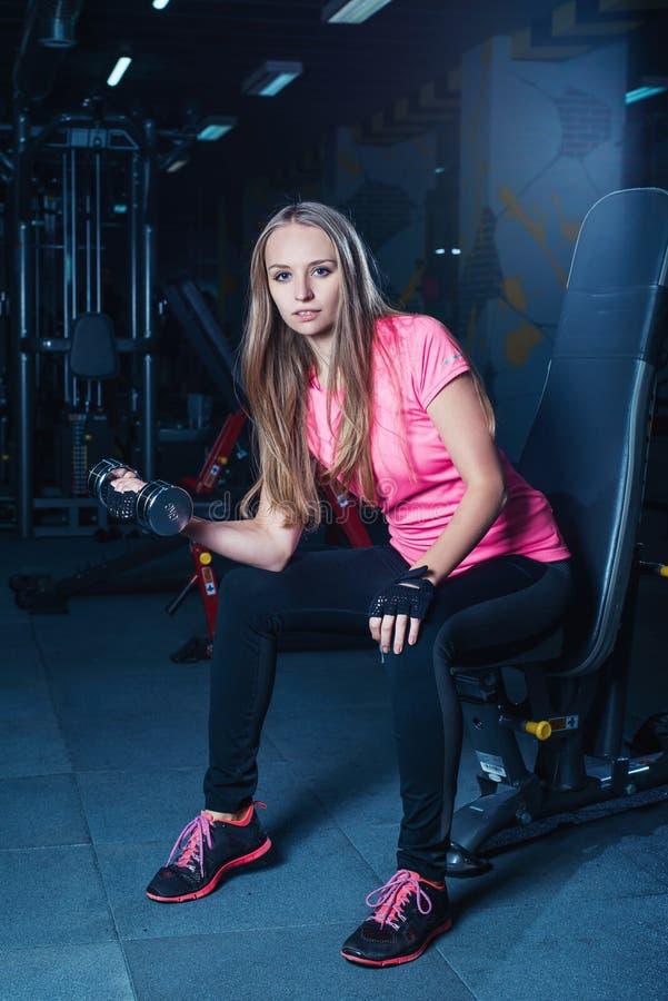 Attraktiv sportig flicka som gör genomkörare med hantlar i idrottshall Härlig konditionkvinna som arbetar på hennes biceps arkivbild