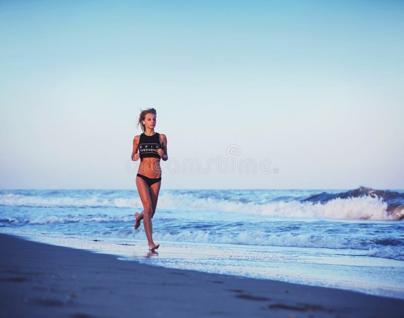 Attraktiv sportig flickakörning längs stranden på den fantastiska solnedgången med havet på bakgrund royaltyfria bilder