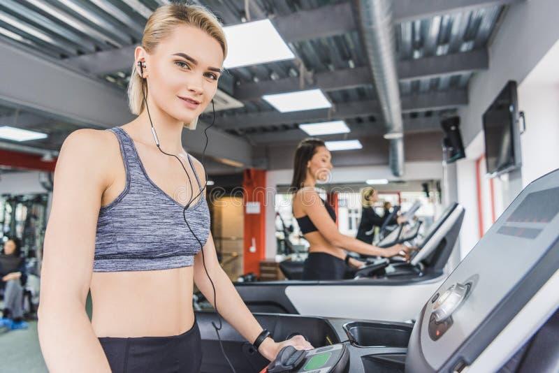 attraktiv sportive kvinnaspring på trampkvarnen på idrottshallen fotografering för bildbyråer