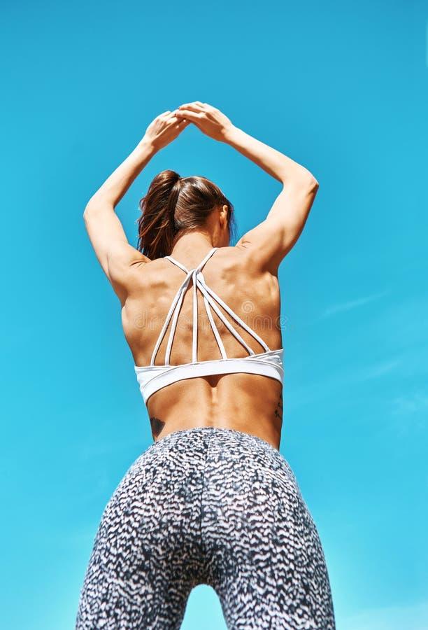 Attraktiv sportkvinna med den brunbrända färdiga kroppen som poserar mot blå himmel tillbaka wiew royaltyfri fotografi