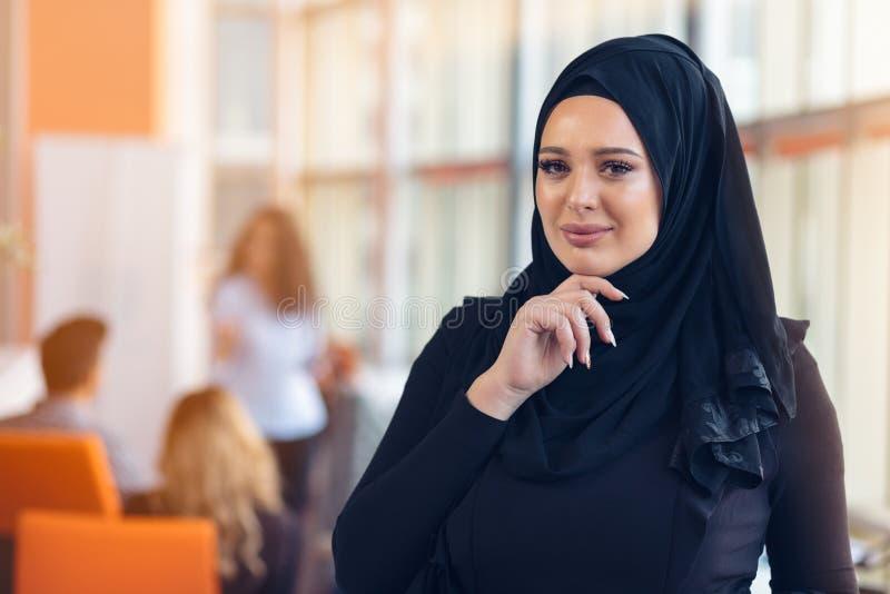 Attraktiv stående av den unga muslimkvinnan med svart hijab på kontoret royaltyfri bild
