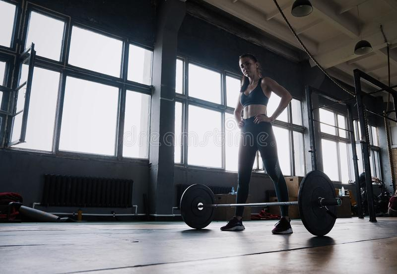 Attraktiv stark muskulös kvinnlig kroppsbyggare som gör tunga squats som lyfter skivstången på crossfitidrottshallen arkivbild