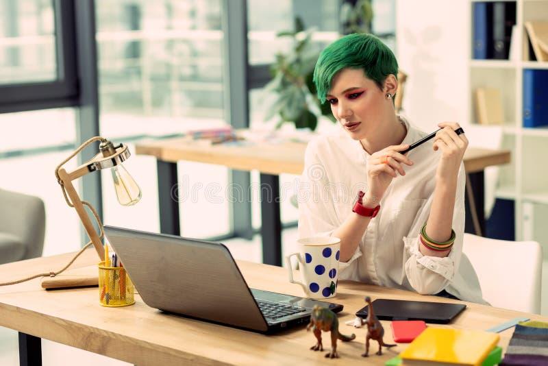 Attraktiv stilfull ung kvinna som arbetar på bärbara datorn royaltyfria foton