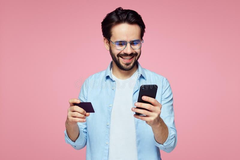 Attraktiv stilig man som rymmer den plast- kreditkorten, och mobiltelefon som isoleras över rosa bakgrund royaltyfri foto