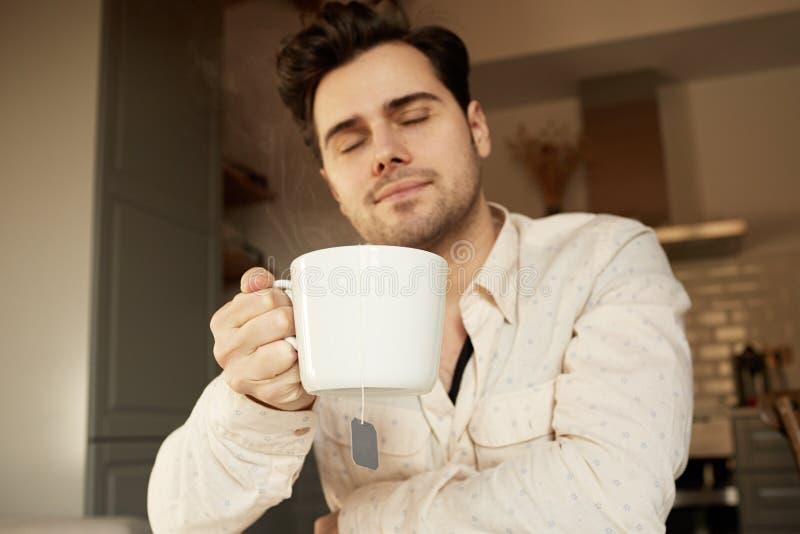 Attraktiv stilig man som rymmer den vita koppen kaffe hemma arkivfoto