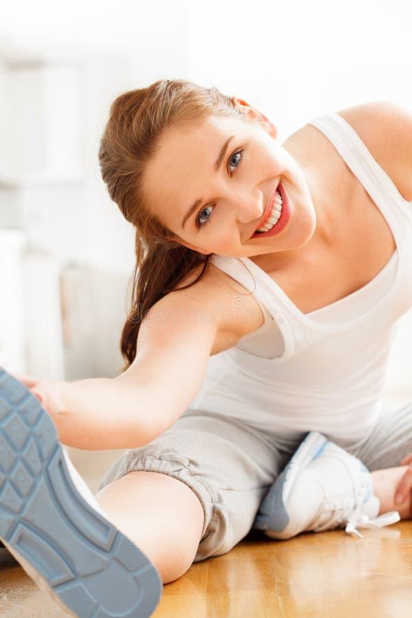 Attraktiv sund ung kvinna som sträcker yogaidrottshall royaltyfri foto