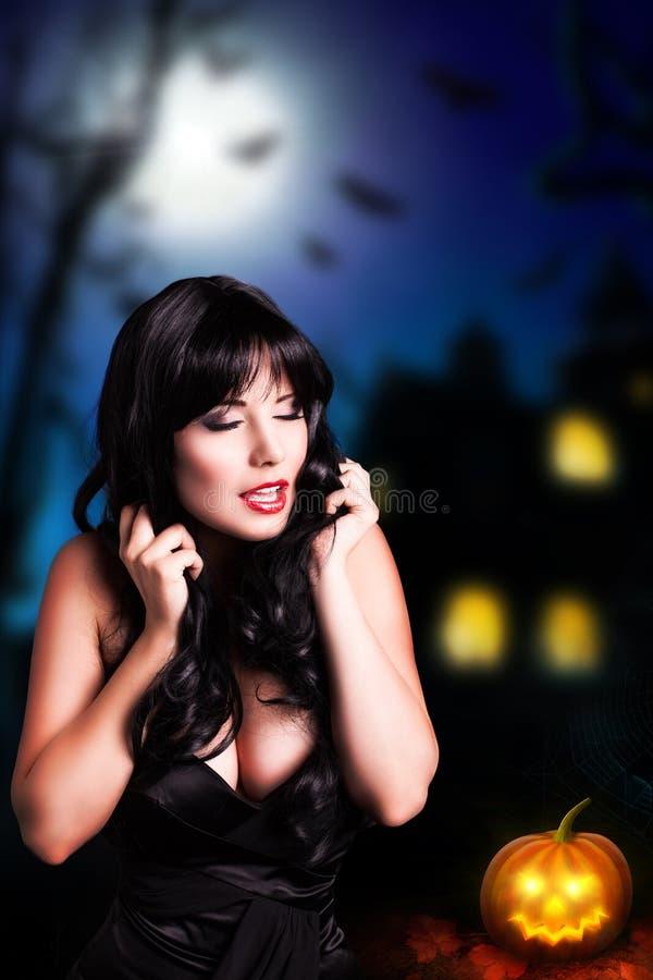 Attraktiv svart haired kvinna framme av ett halloween hus arkivbild