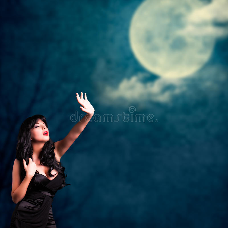 Attraktiv svart haired kvinna och en fullmåne arkivbilder