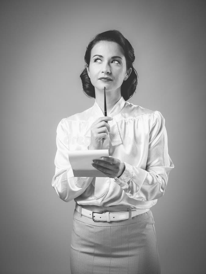 Attraktiv tappningsekreterare som tar anmärkningar arkivbild