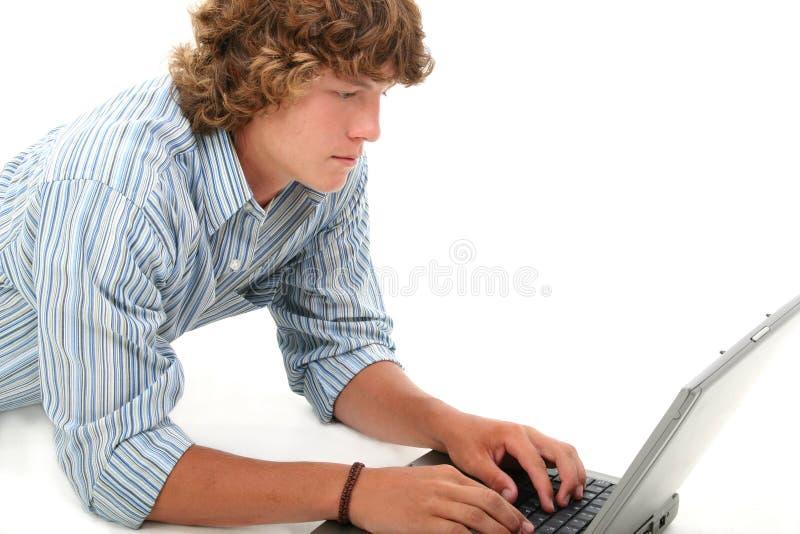 attraktiv teen pojkedatorbärbar dator royaltyfri bild