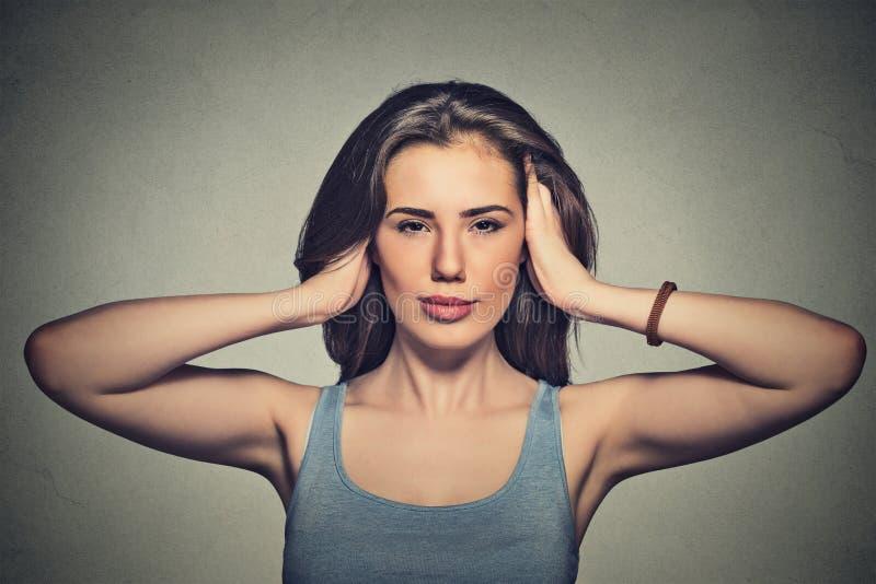 Attraktiv tillfällig kvinnabeläggning med händer henne öron royaltyfria bilder