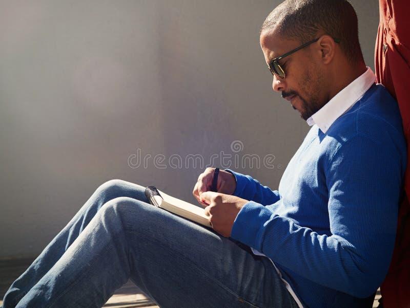 Attraktiv tillfälligt klädd ung amerikansk afrikansk man med solglasögon som gör anmärkningar i förskriftsbok Student som förbere royaltyfri bild