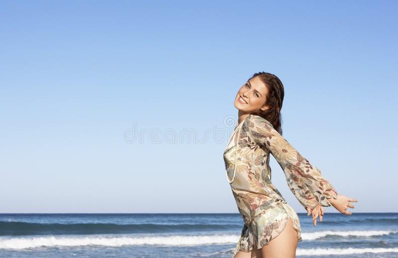 Attraktiv tonårs- flicka med utsträckt posera för armar vid havet royaltyfri foto