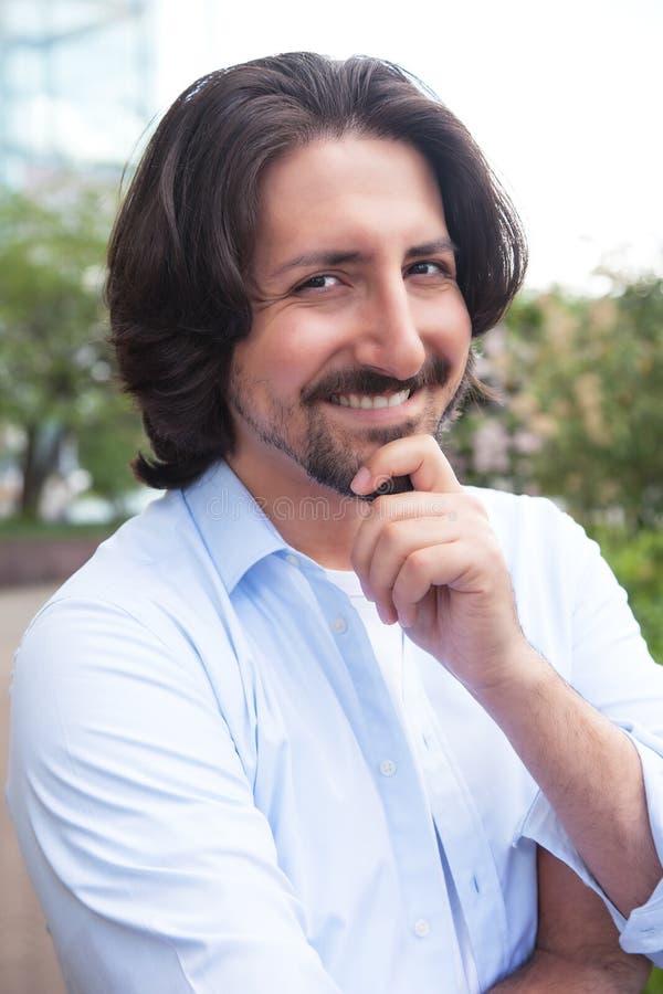 Attraktiv turkisk man med skägget som skrattar utomhus på kameran royaltyfria bilder
