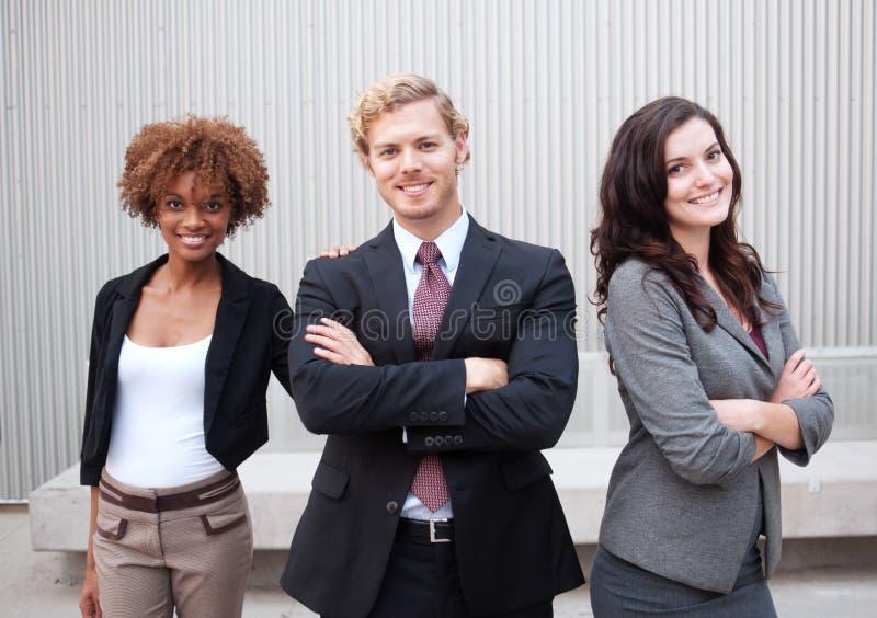 Attraktiv ung affärsgrupp som tillsammans står på kontoret arkivbilder