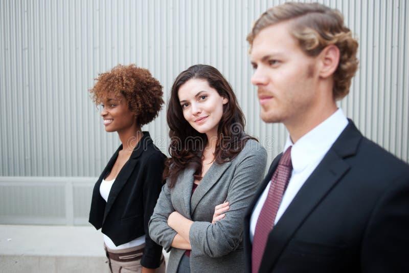 Attraktiv ung affärsgrupp som tillsammans står på kontoret arkivfoto