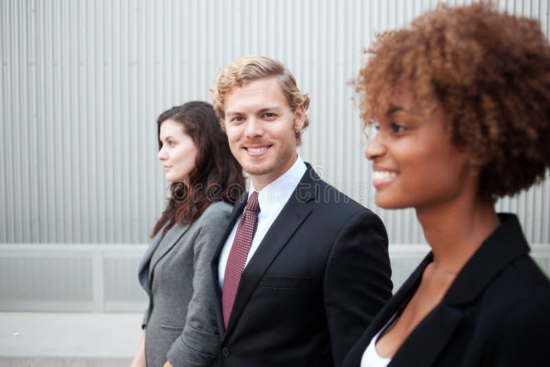 Attraktiv ung affärsgrupp som tillsammans står på kontoret arkivfoton