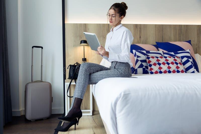Attraktiv ung affärskvinna som använder hennes digitala minnestavla som sitter på sängen på hotellrum arkivbild