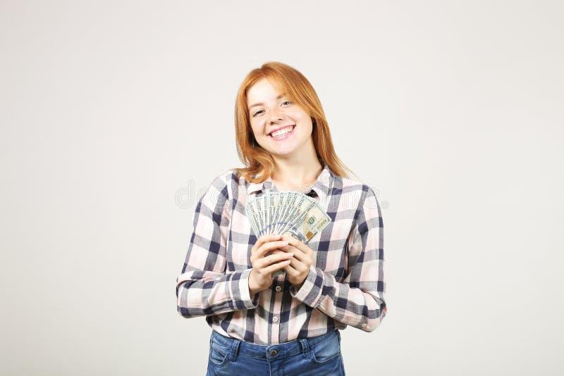 Attraktiv ung affärskvinna som poserar med gruppen av händer för USD kassa som in visar positiva sinnesrörelser och lyckligt ansi arkivfoton