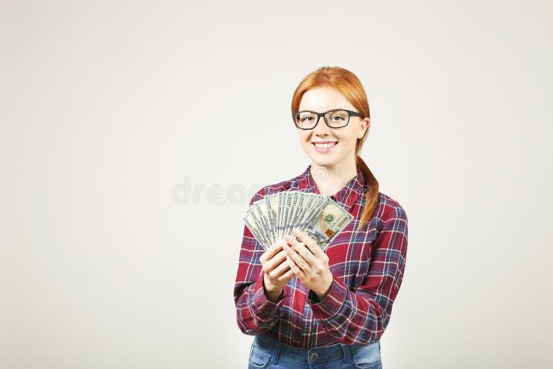 Attraktiv ung affärskvinna som poserar med gruppen av händer för USD kassa som in visar positiva sinnesrörelser och lyckligt ansi royaltyfri fotografi