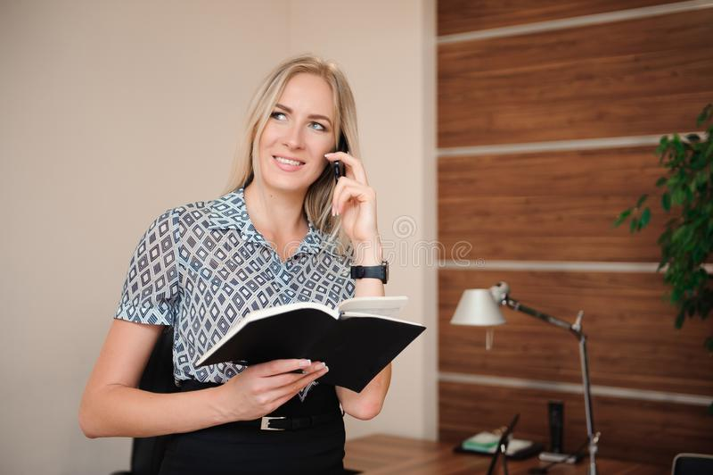 Attraktiv ung affärskvinna Working på affärsdokumenten på hennes skrivbord inom kontoret royaltyfri fotografi