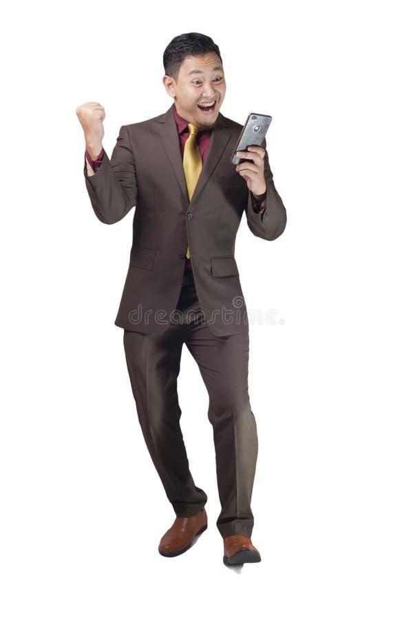 Attraktiv ung affärsman att motta goda nyheter på hans telefon, lycklig segra gest fotografering för bildbyråer