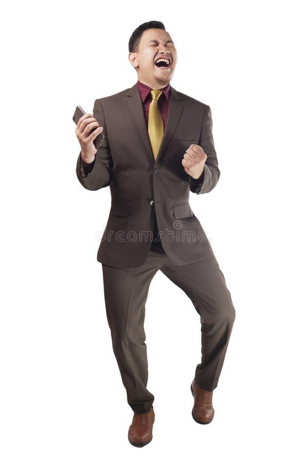 Attraktiv ung affärsman att motta goda nyheter på hans telefon, lycklig segra gest arkivfoton