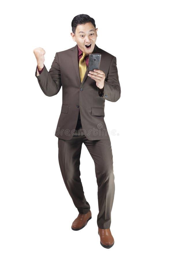 Attraktiv ung affärsman att motta goda nyheter på hans telefon, lycklig segra gest arkivfoto