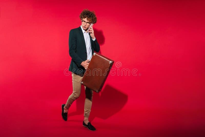 Attraktiv ung affärsman i den vita skjortan som går med resväskan royaltyfri foto