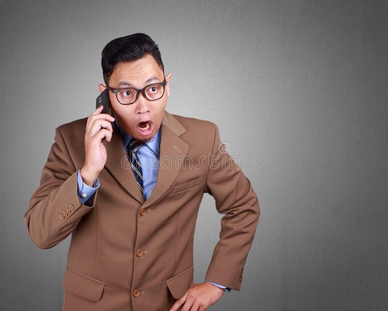 Attraktiv ung affärsman som talar på hans telefon, chockad expre arkivbild
