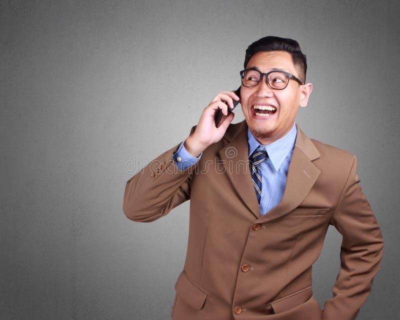 Attraktiv ung affärsman som talar på hans telefon, lyckligt le royaltyfri fotografi