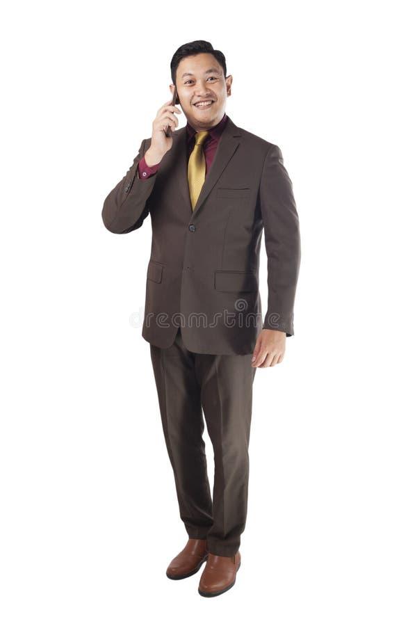 Attraktiv ung affärsman som talar på hans telefon, lyckligt le arkivfoto